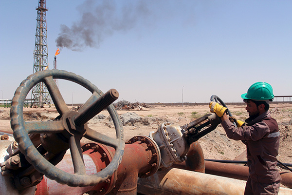 A worker checks the valve of an oil pipe at Al Sheiba oil refinery in the southern Iraq city of Basra